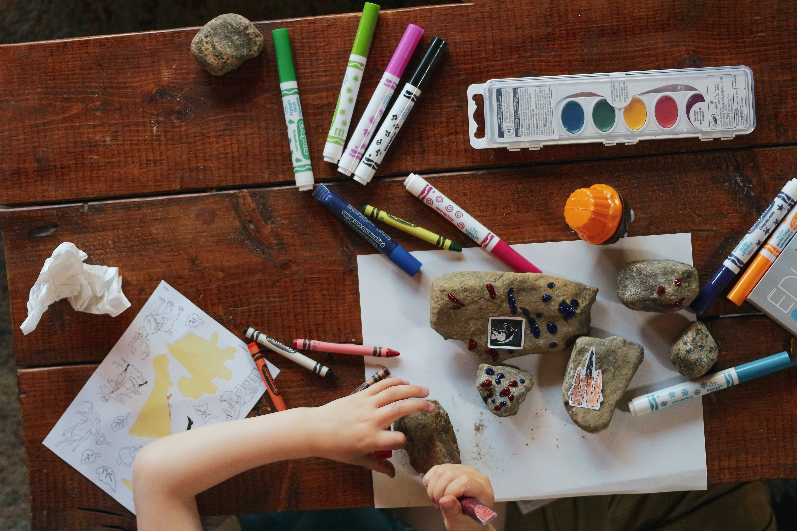Kid drawing, crafting, and painting rocks.