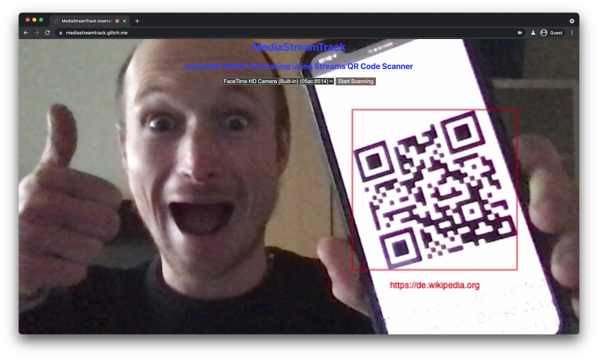 QR code scanner running in desktop browser tab showing a detected and highlighted QR code on the phone the user holds in front of the laptop's camera.