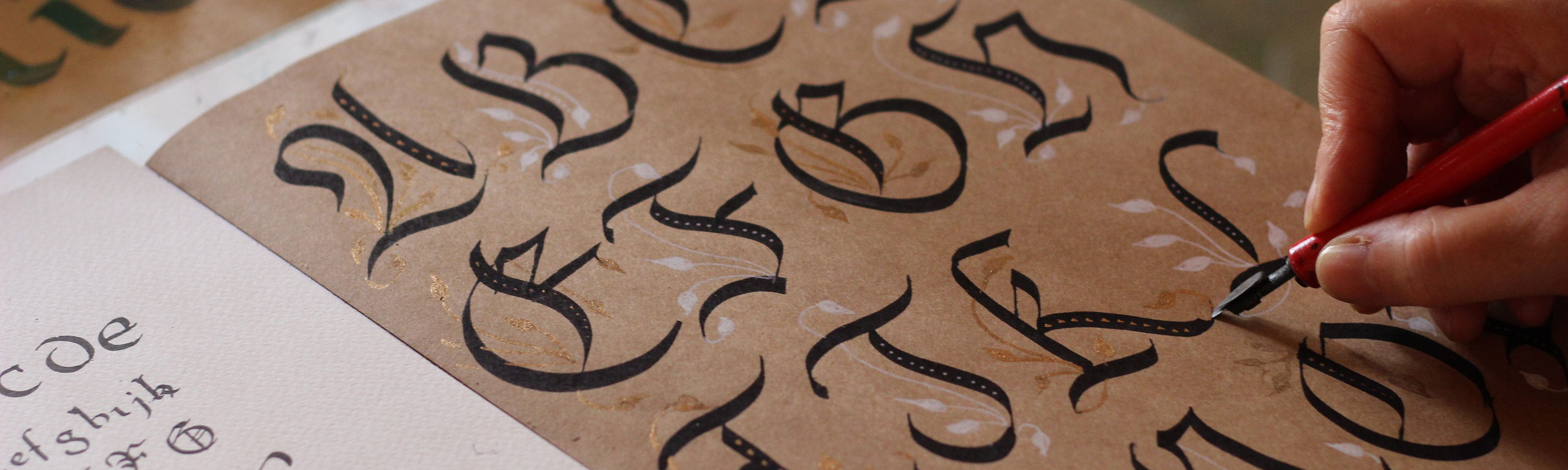 A hand draws letters in calligraphic script on paper.