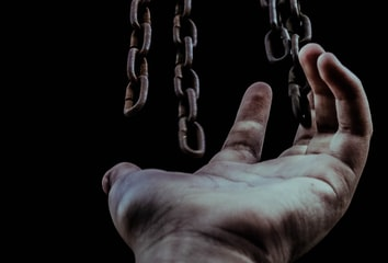 A hand and several hanging chains, symbolizing links.