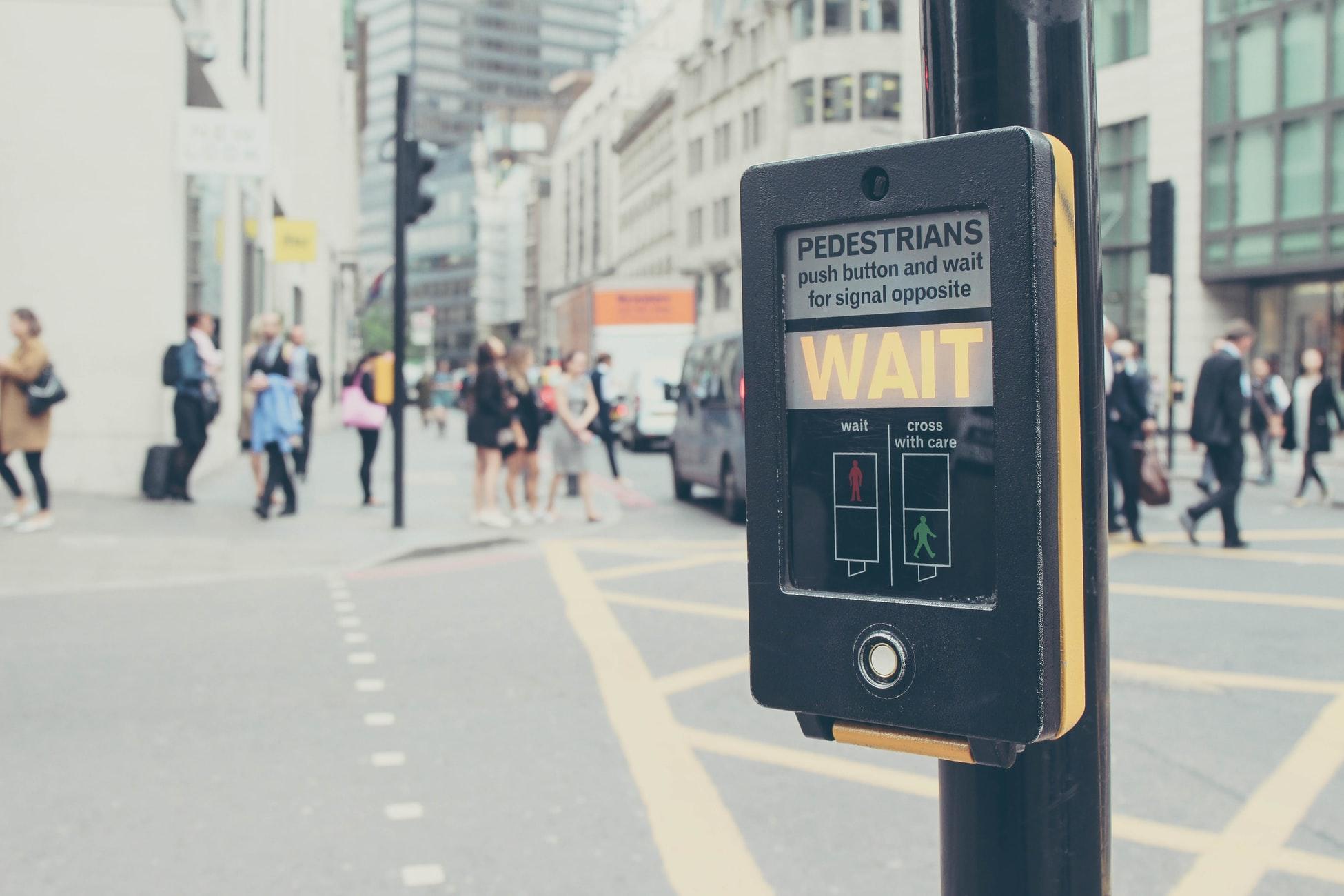 A crosswalk signal asking pedestrians to wait.