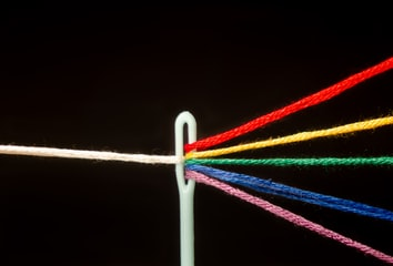 A needle acting as a prism—splitting a single white thread into multiple colourful ones.