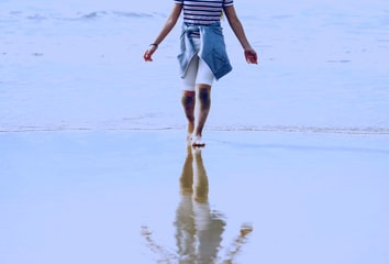 A person and their refection on wet sand, symbolizing the migration from the legacy to the new Reporting API.