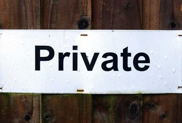 A black-on-white printed sign saying Private, on a wooden wall.