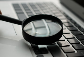 Inspecting a laptop with a magnifying glass.