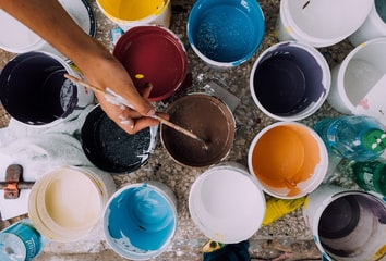 A hand dipping a paintbrush in one of several buckets of paint.