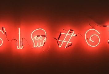 Neon lights shaped into various symbols that are commonly used in passwords.