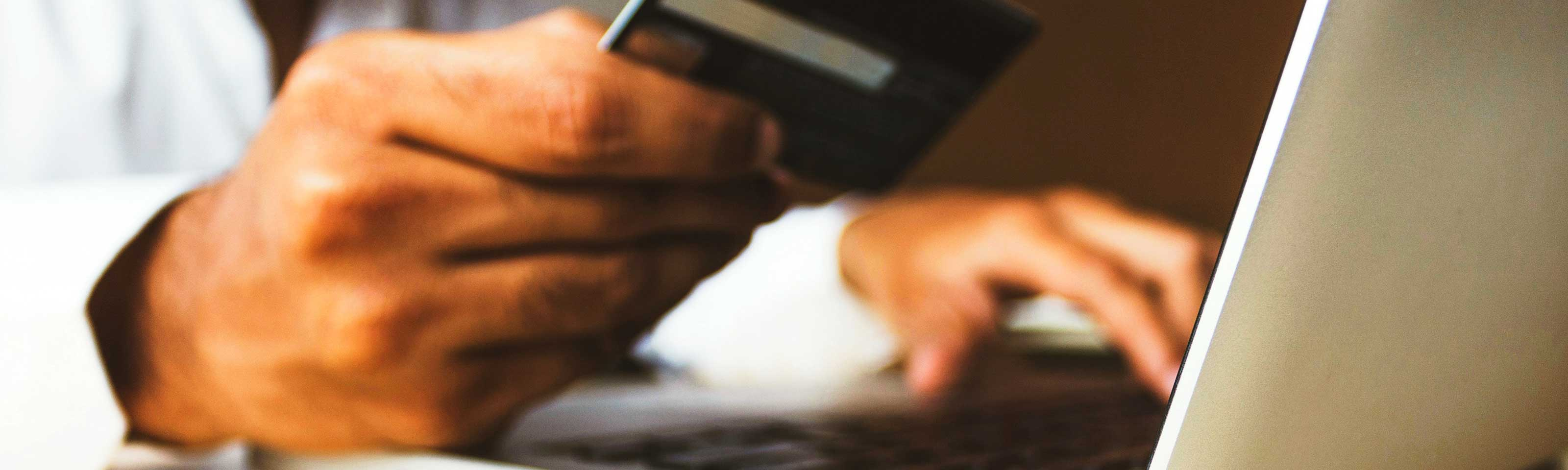 Businessman using a payment card to make a payment on a laptop computer.