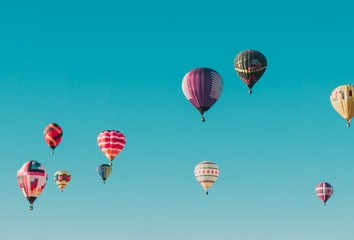 A group of colorful hot air balloons launching into the sky.