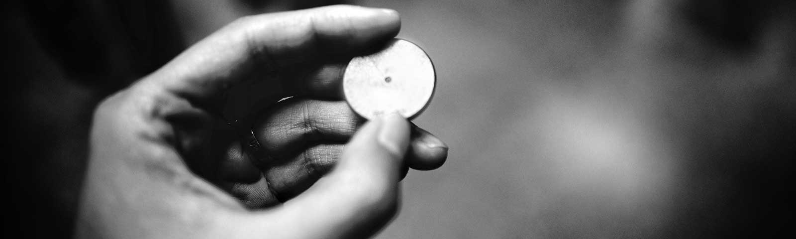 Black and white photograph of hand holding token
