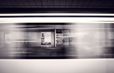 A long-exposure shot of a moving subway train and advertisement posters at the station photo.