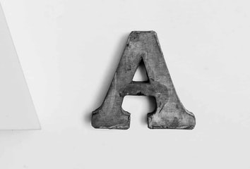 A large letter A from a type set sitting on a white table.