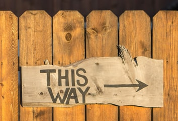 """A photo of a brown wooden plank fence, with a signboard attached to it. The signboard reads """"this way"""", with an arrow pointing to the right."""