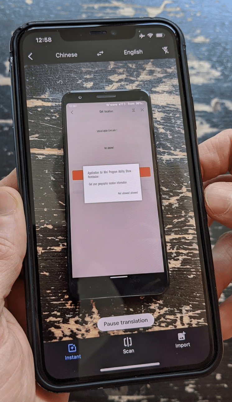 A secondary phone running Google Translate in camera mode live-translating the user interface of a Chinese mini app running on the primary phone.
